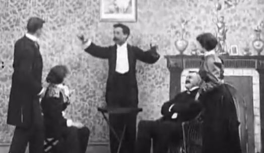 Walter R. Booth (probably), centre, playing the magician in Upside Down; or, the Human Flies (1899)
